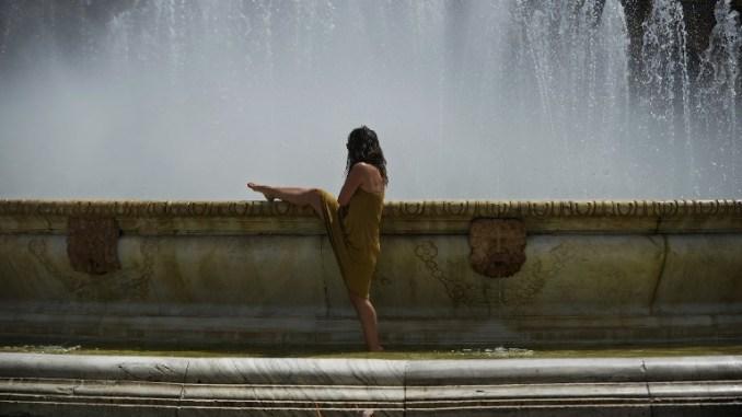 Женщина охлаждается в фонтане в Севилье. Фото: AFP