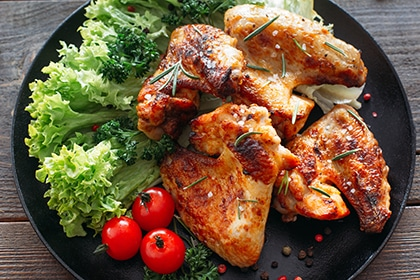 Grilled chicken wings with fresh vegetables. Baked chicken meat with lettuce and tomatoes cherry. Homemade meat on wooden table.