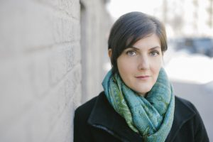 An author photo of Erika Swyler with short brown hair and bright blue scarf.