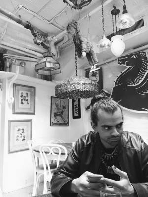 A black and white author photo of Joey De Jesus, a person with dark hair pulled back in a bun with dark eyes and slight mustache, wearing a leather jacket, holding a smart phone, sitting at a table in a space with a high ceiling with an array of hanging lamps, exposed pipes, and a large cut-out of a flying horse and on the wall.