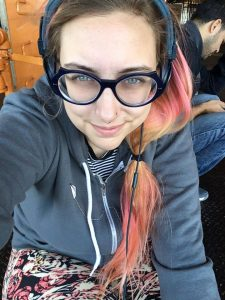Author photo for Allison Bird Treacy, a blue-eyed woman with large, round, black glasses, a long, pink and yellow side ponytail, wearing a slate gray hooded top, over a blue and white striped shirt, slate headphones that nearly match the hoodie, and black leggings featuring a pink and white flower pattern.