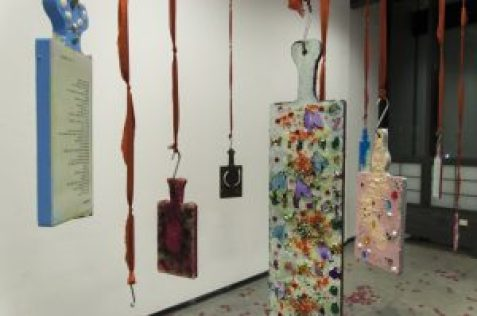 A closer shot photograph of the Conclusions and Findings exhibition. Several paddles can be scene with decorated backs and one front facing poem. Hung from their handles by red ribbons. Flower petals are scattered beneath them on the exhibit space floor.