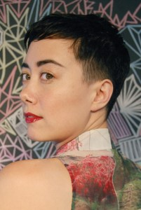A photo of the author, a mixed-race Asian genderfluid person with short hair, Addie's body is facing away from the camera, and Addie is looking over their shoulder toward the camera. Addie is wearing red lipstick.