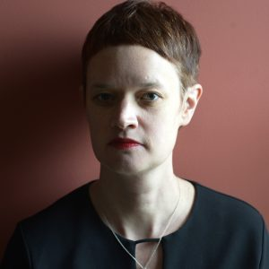Photo of the author, Carley Moore, with short auburn hair and light skin. Half of her face is in shadow.