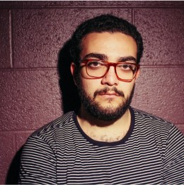 A photo of the author, an Egytian person with a beard in front of a purple wall, wearing red glasses and a striped shirt