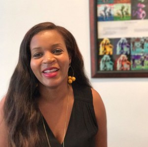 A photograph of the author, Kwoya Fagin Maples, a Black woman with long hair, smiling. Art is visible behind her, and she's wearing a sleeveless black shirt.