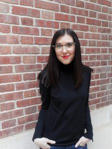 A photo of a woman wearing glasses and a black sweater, standing against a brick wall