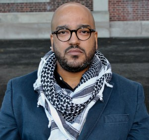 A photo of the author, a man of color, wearing a white and black scarf and dark rimmed glasses, with brick walls behind him. He's looking straight into the camera.