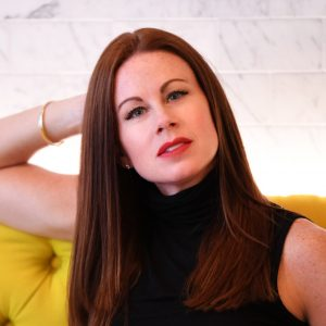 A photo of Britt Tisdale, a woman with long brown hair and light skin, wearing red lipstick, posing with her arm behind her head, sitting on a yellow tufted sofa.
