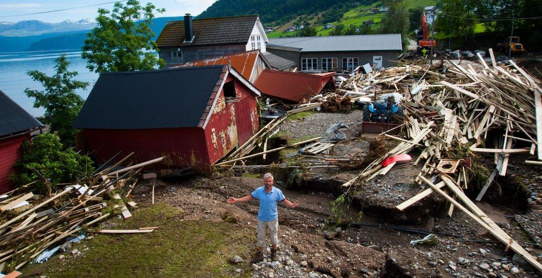 Oddbjørn Bruset foran flomskadet hus og naust.