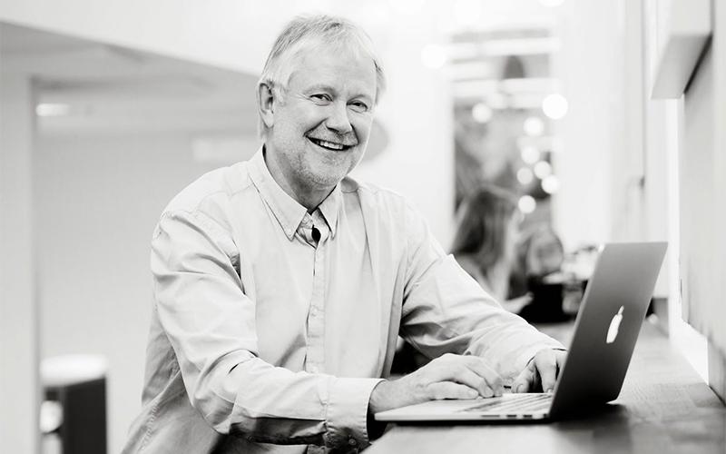Svart-hvit bilde av Arne Krokan ved en mac.