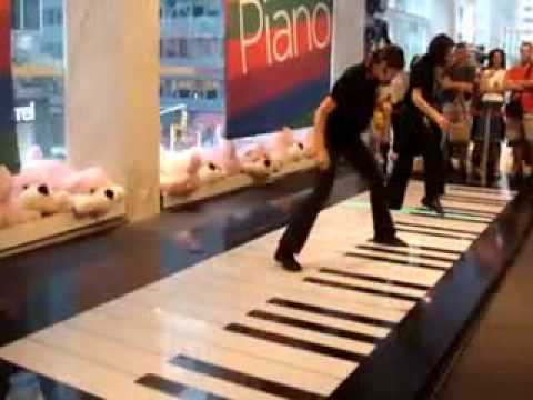 Two Galz Dancing On A Big Piano