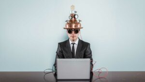 Business man at a computer with an invention on his head to show he is using technology.