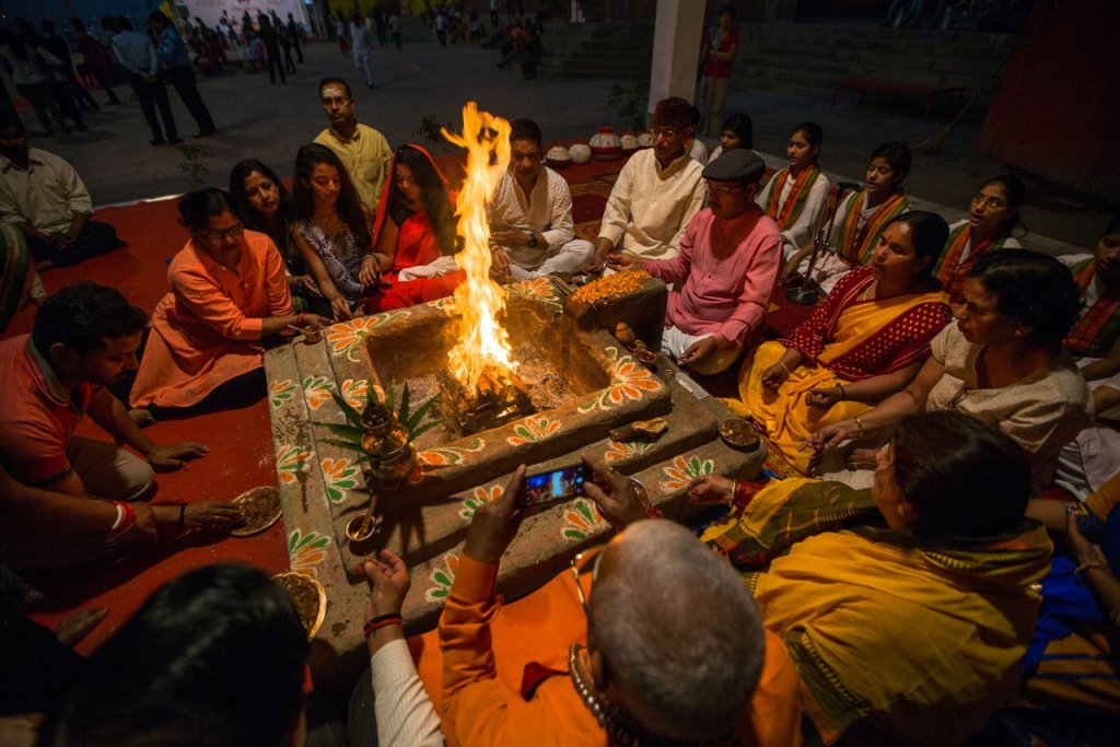 VARANASI, INDIA – MAR 22, 2018: People sit near a ceremonial fir