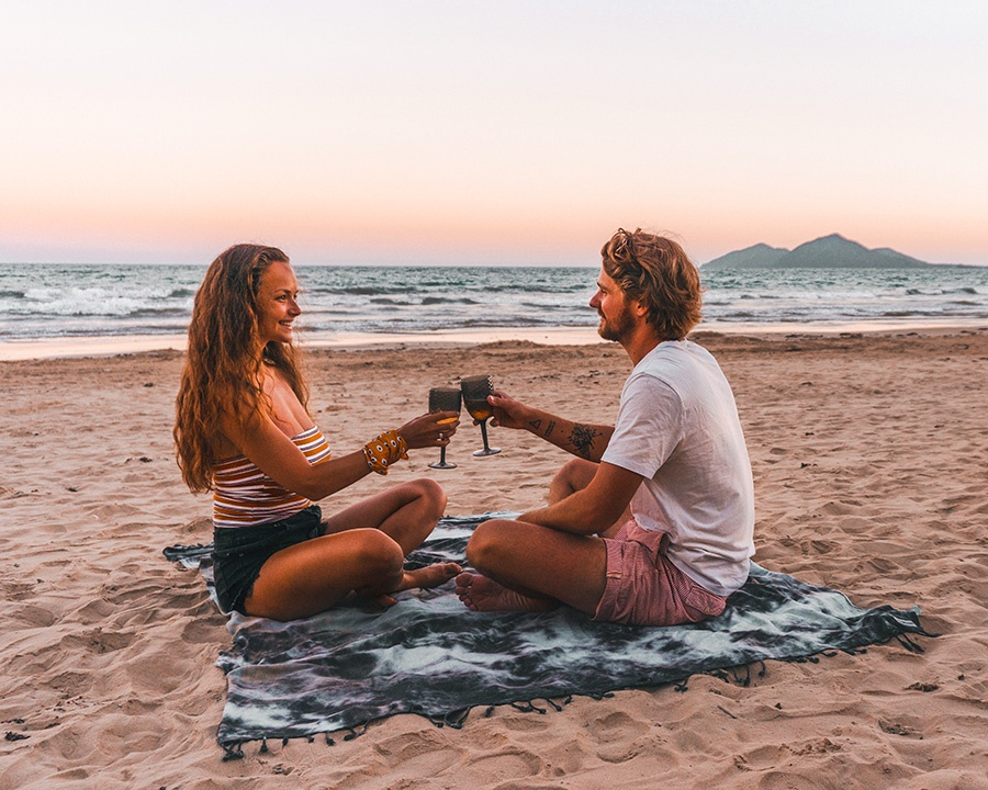 man_and_woman_sitting_on_beach_while_toasting_wine_glasses-scopio-09afd277-24c5-4f83-99df-9077462adee0-PICCOLA