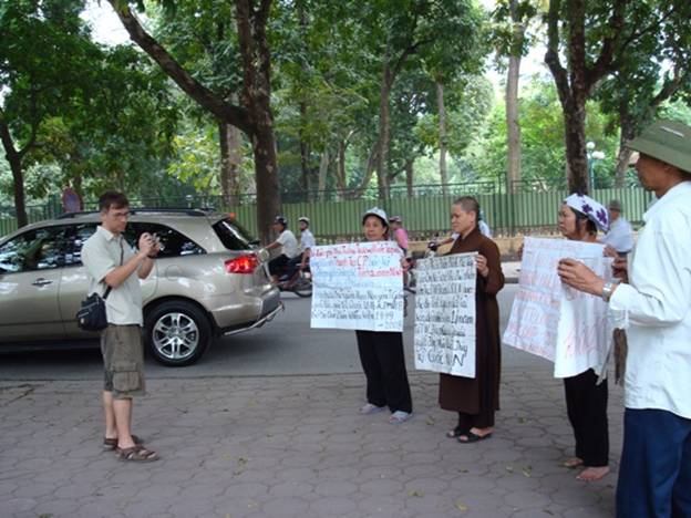 Hình phóng viên nước ngoài đến hỏi thăm Dân Oan bằng tiếng Việt và sau đó xin phép chụp những tấm biểu ngữ. Cũng vì những bức hình này, trụ số tiếp dân, số 1 Mai Xuân Thưởng, phải cấp tốc dời về 110 Cầu Giấy.