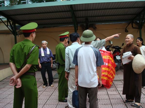 Hình gia đình Dân Oan Trương Thị Quý bị côn an cướp biểu ngữ tại trụ sở tiếp dân 110 Cầu Giấy, Sư Bình đến tiếp cứu bằng những lời lẽ đanh thép, bọn côn an phải chùng tay.