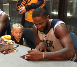 C.J. Miles signs autographs with the help of his special friend.