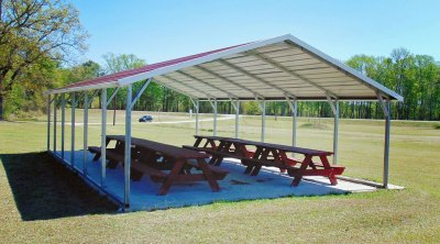 picnic tables under metal carport in park