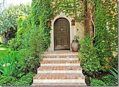 Porta antiga envolta por trepadeiras verdes