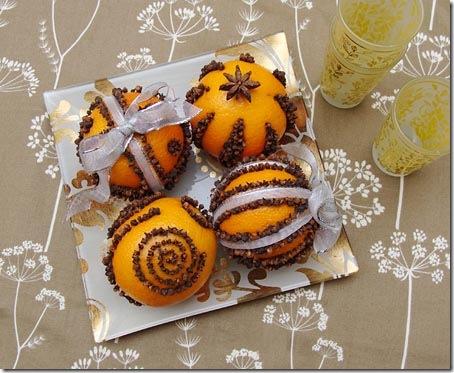 Arranjo de mesa com laranjas, cravos, anis estrelados e fitas decorativas