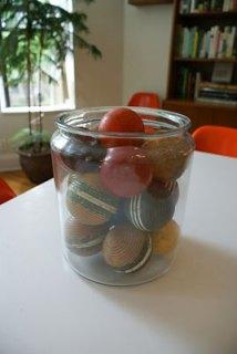 Coleção de bolas de cerâmica e madeira dentro de um pote de vidro