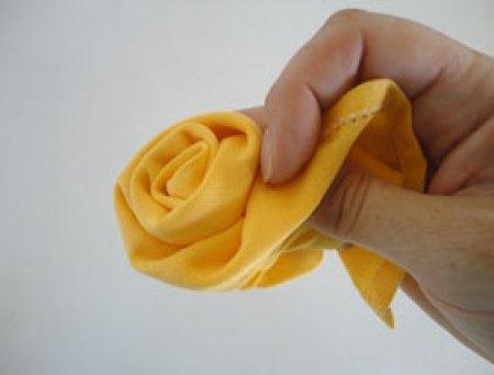 Siga dobrando as bordas e enrolando o tecido