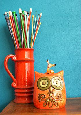 Agulhas de tricô ficam bem acomodadas dentro de uma caneca de cerâmica
