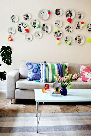 Pratos na parede enfeitados com pom-pons coloridos