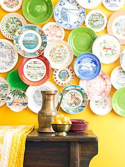 Pratos de recordação de viagens decorando a parede da sala