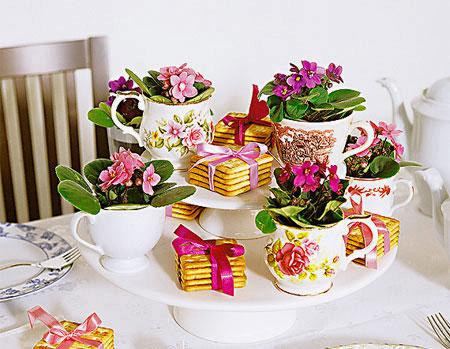 Aparelhos de chá e suportes de bolo montam o arranjo de mesa