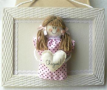 Bonequinho de pano no quadro de quarto de bebê