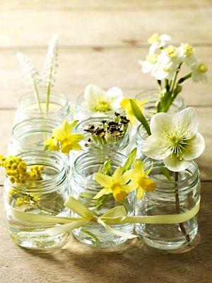 Potes de vidro amarrados com fita de cetim para servir de vaso