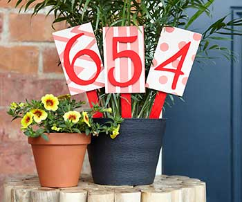 Números da casa em plaquinhas dentro de vasos