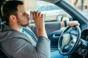 man distracted while driving - dangers of distracted driving in florida - viles and beckman - fort myers