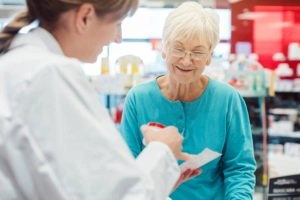 Senior woman in pharmacy talking to the chemist or pharmacist ex