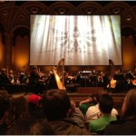 The orchestra awaits the conductor to begin the Symphony