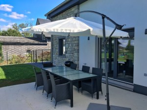 large terrace with dining table, chairs, barbecue, sunshades