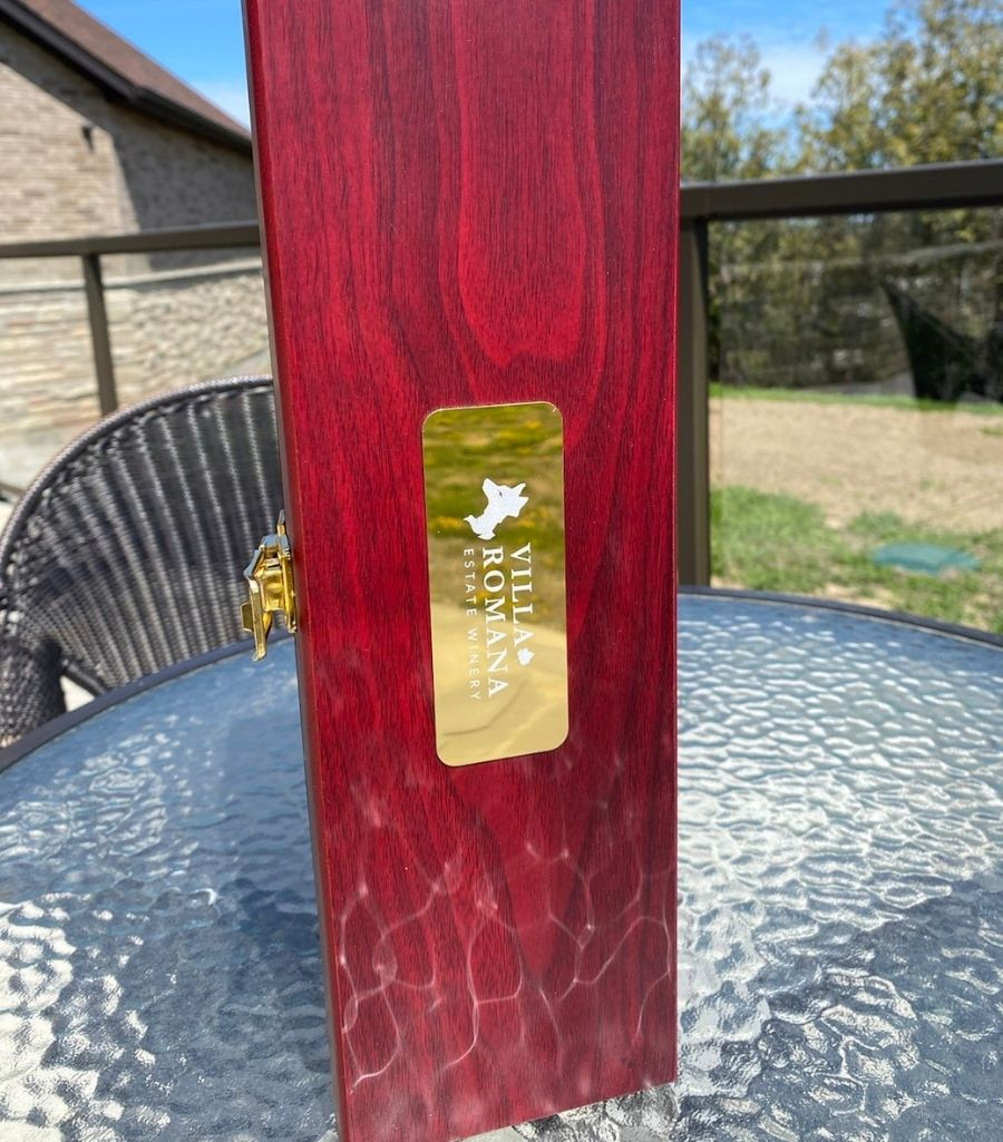 Wine box made of rosewood, with a bronze label featuring the Villa Romana Estate Winery logo and lettermark, sitting on a glass table outdoors.