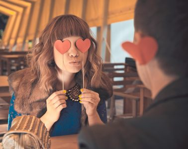 Young kissing happy couple in love sitting in cafe in sunny evening
