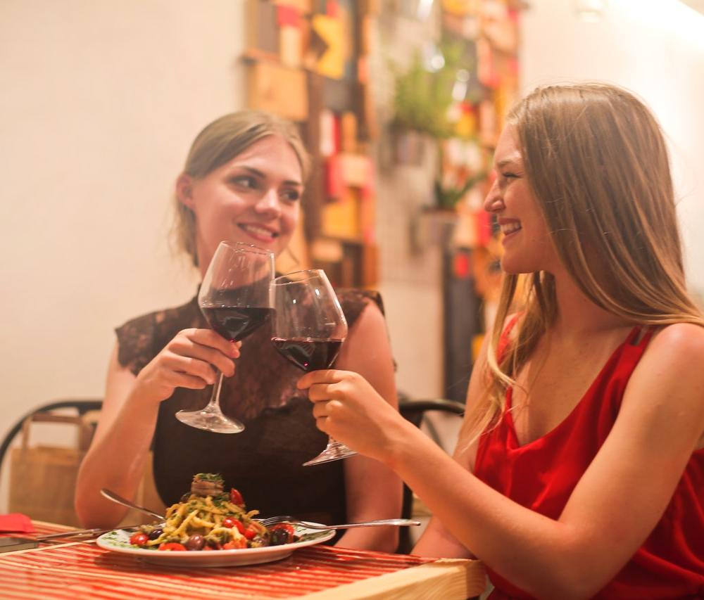 women drinking red wine. they are smiling knowing that red wine could help them fight against depression, anxiety and stress