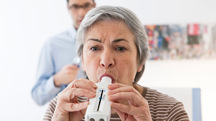 old woman using an inhaler