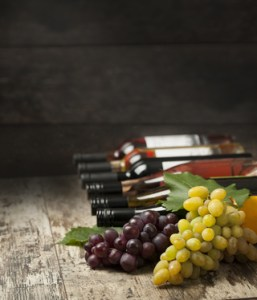 Bottles of wine and grapes on wooden background