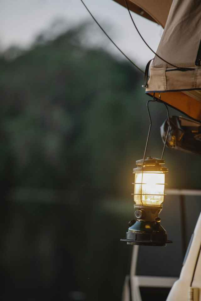 retro lamp hanging from tent during camping in nature in evening