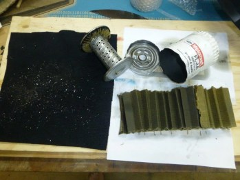 Part of my service procedure for Tudor Rose is to cut the oil filter open, wash all parts in petrol and strain through a black cloth to look for metal particles etc which is a clear indication of what is happening within the engine. This is what I found, particles of aluminium obviously from the bearings.