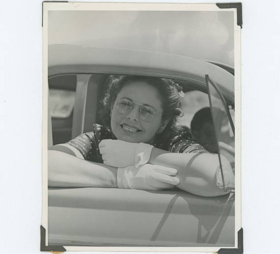 1950s vintage image of woman in a car wearing glasses