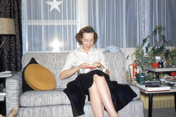 1950s photo of a woman on a couch wrapping a christmas present