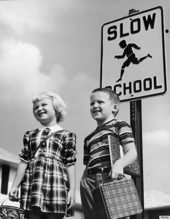 circa 1955: A little girl and boy carrying a lunch pails and notebooks stand near a school zone traffic sign.