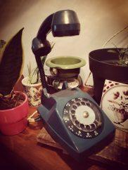 blauwe petrol vintage telefoon, met op de achtergrond bloempotten