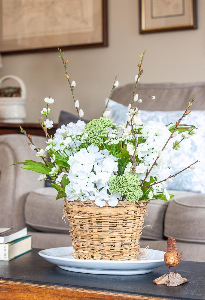 Spring flower arrangement in a woven basket on an Ironstone platter